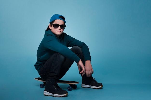 Vue de face du garçon moderne assis sur une planche à roulettes