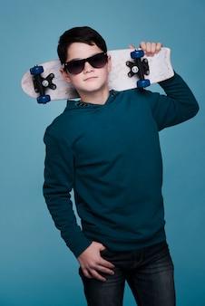 Vue de face du garçon moderne avec des lunettes de soleil posant