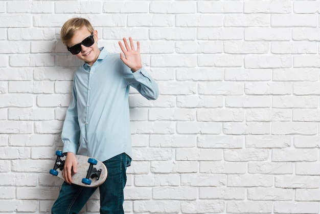 Vue de face du garçon moderne avec planche à roulettes et espace copie