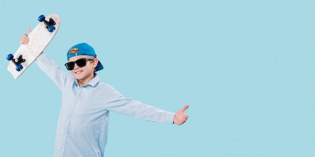 Vue de face du garçon moderne avec planche à roulettes avec espace copie