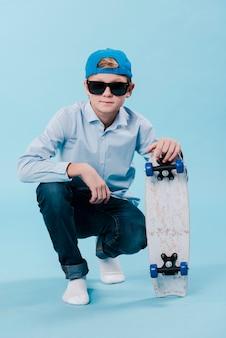 Vue de face du garçon moderne avec planche à roulettes