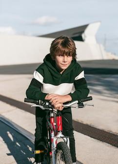 Vue de face du garçon posant assis sur son vélo