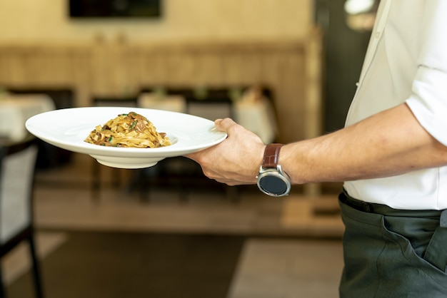 Vue de face du garçon tenant une assiette avec des pâtes