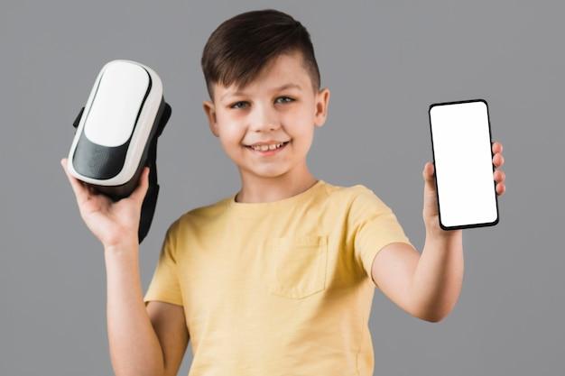 Vue de face du garçon tenant un casque et un smartphone de réalité virtuelle