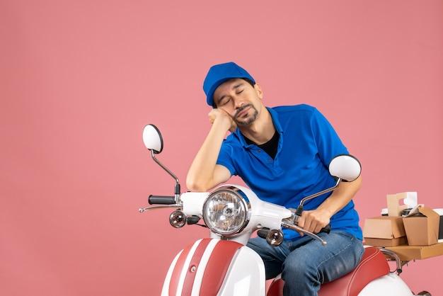 Vue de face du gars de messagerie endormi portant un chapeau assis sur un scooter sur fond de pêche pastel