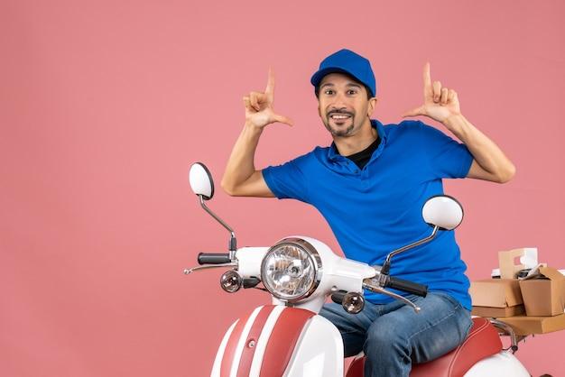 Vue de face du gars de messagerie souriant et heureux portant un chapeau assis sur un scooter sur fond de pêche pastel