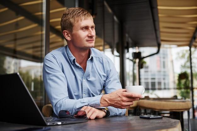 Vue de face du gars qui est dans un café moderne avec son ordinateur portable pendant la journée.