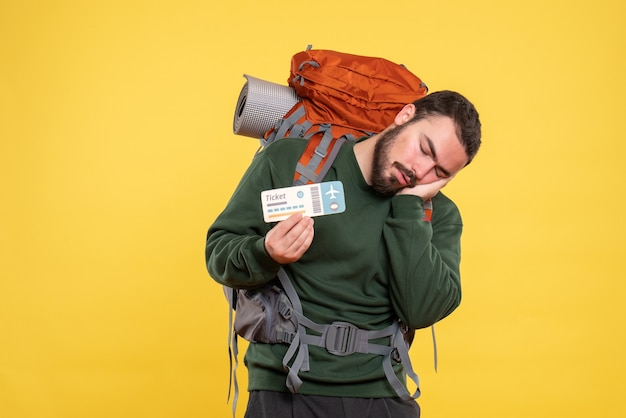 Vue de face du gars de voyage fatigué avec sac à dos dormant sur fond jaune