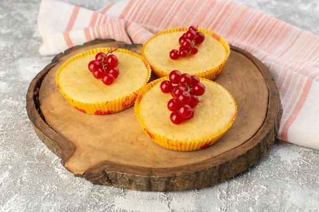 Vue de face du gâteau aux canneberges délicieux cuit sur la planche de bois et surface grise