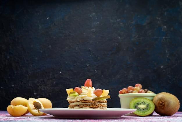 Vue de face du gâteau à la crème et aux fruits sur la surface sombre