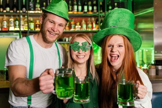 Vue de face du groupe d'amis célébrant st. le jour de patrick avec des boissons