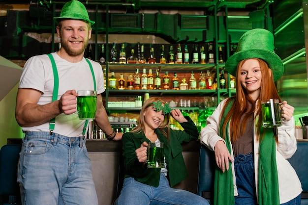 Vue de face du groupe d'amis célébrant st. patrick's day au bar avec boissons