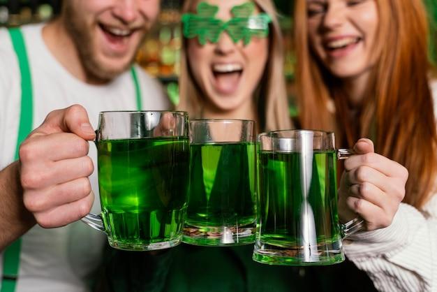 Vue de face du groupe d'amis célébrant st. patrick's day avec boissons au bar