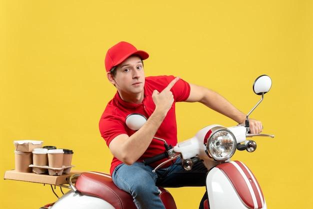 Vue de face du jeune adulte surpris portant un chemisier rouge et un chapeau livrant des commandes pointant vers le haut sur fond jaune