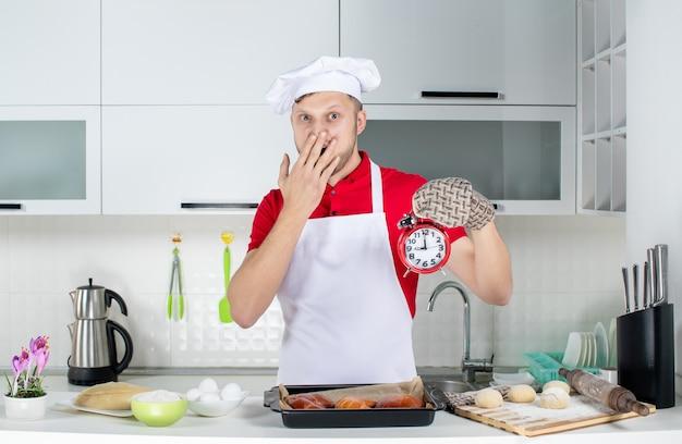 Vue de face du jeune chef masculin surpris portant un support tenant une horloge dans la cuisine blanche