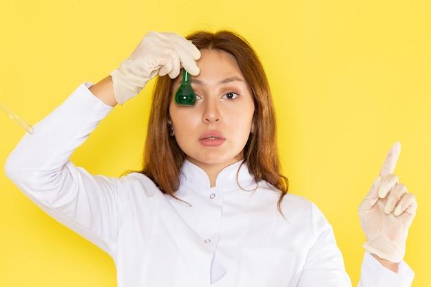 Vue de face du jeune chimiste en costume blanc tenant des solutions chimiques