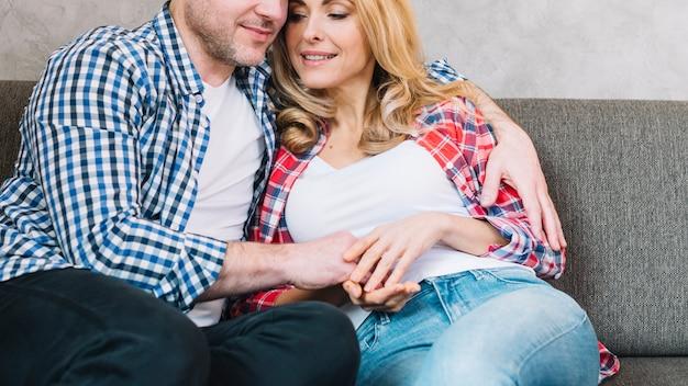 Vue de face du jeune couple d'amoureux assis sur un canapé