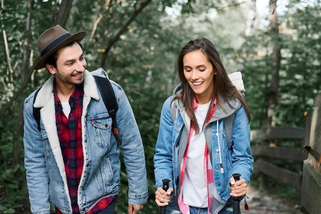 Vue de face du jeune couple en randonnée dans la forêt