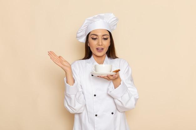 Vue de face du jeune cuisinier en costume de cuisinier blanc tenant une tasse de café sur le mur blanc clair