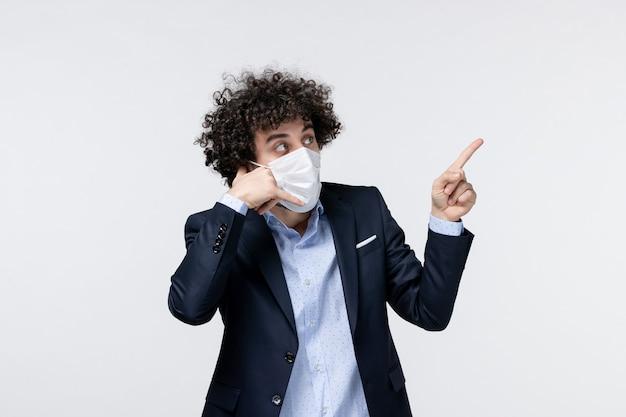 Vue de face du jeune entrepreneur masculin en costume et pointant vers le haut sur une surface blanche