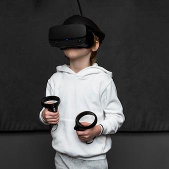 Vue de face du jeune garçon à l'aide d'un casque de réalité virtuelle