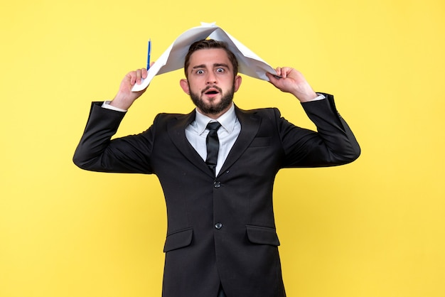 Vue de face du jeune homme d'affaires devient fou toucher la tête avec des feuilles de papier blanc sur jaune