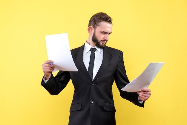 Vue de face du jeune homme d'affaires examine attentivement chaque document sur jaune