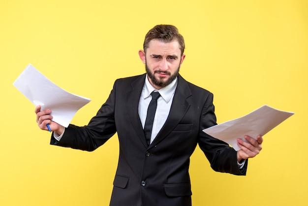Vue de face du jeune homme d'affaires incertain tenant du papier blanc dans les deux mains sur jaune