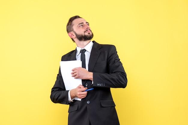 Vue de face du jeune homme d'affaires portant un costume en levant et en pensant à de nouvelles idées tenant du papier blanc avec un stylo sur jaune