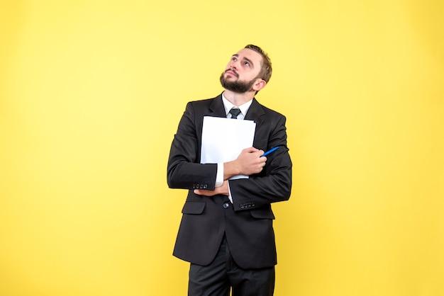 Vue de face du jeune homme d'affaires réfléchie portant un costume en levant et tenant du papier blanc avec un stylo sur jaune