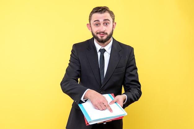 Vue de face du jeune homme d'affaires avec un sourire pointe avec optimisme avec un doigt vers les documents sur jaune
