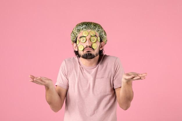 Vue de face du jeune homme appliquant un masque de concombre sur son visage sur un mur rose