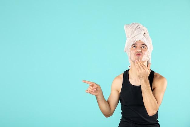 Vue de face du jeune homme après la douche en appliquant de la crème sur son visage sur un mur bleu