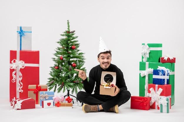 Vue de face du jeune homme assis autour de cadeaux sur un mur blanc