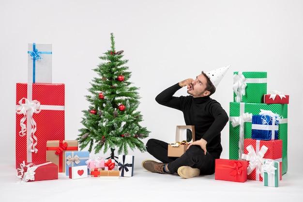 Vue de face du jeune homme assis autour des cadeaux de vacances sur le mur blanc