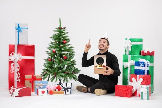 Vue de face du jeune homme assis autour de vacances cadeaux holding package avec jouets sur mur blanc