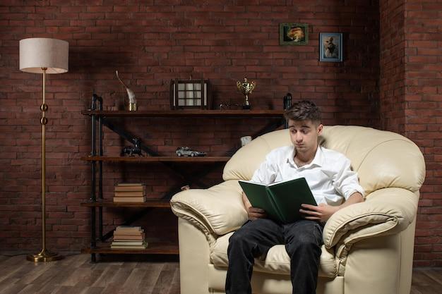 Vue de face du jeune homme assis sur le canapé et livre de lecture à l'intérieur de la chambre travail du soir
