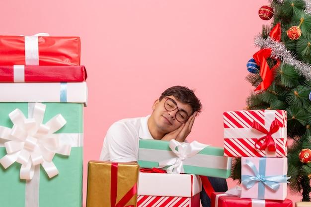 Vue de face du jeune homme autour de cadeaux et arbre de noël sur le mur rose