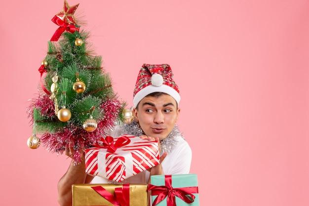Vue de face du jeune homme autour des cadeaux de noël et arbre de vacances sur un mur rose