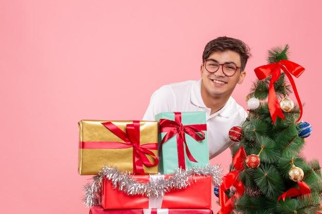 Vue de face du jeune homme autour des cadeaux de noël et arbre de vacances sur mur rose
