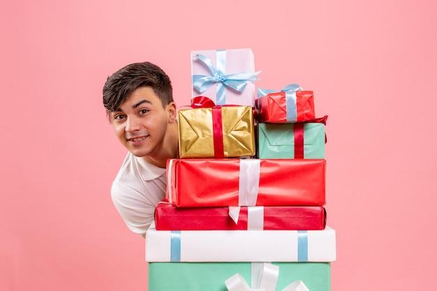 Vue de face du jeune homme autour de cadeaux de noël sur mur rose