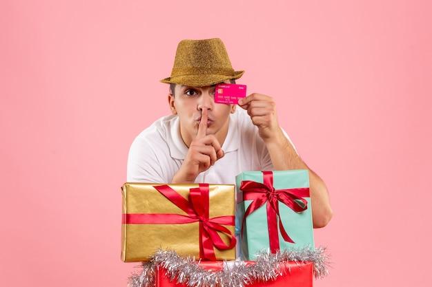 Vue de face du jeune homme autour de cadeaux de noël tenant une carte bancaire sur le mur rose