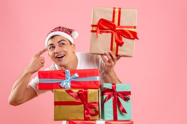 Vue de face du jeune homme autour de différents cadeaux de noël sur le mur rose