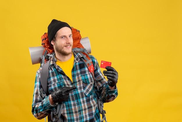 Vue de face du jeune homme barbu avec backpacker et chapeau noir tenant une carte de crédit