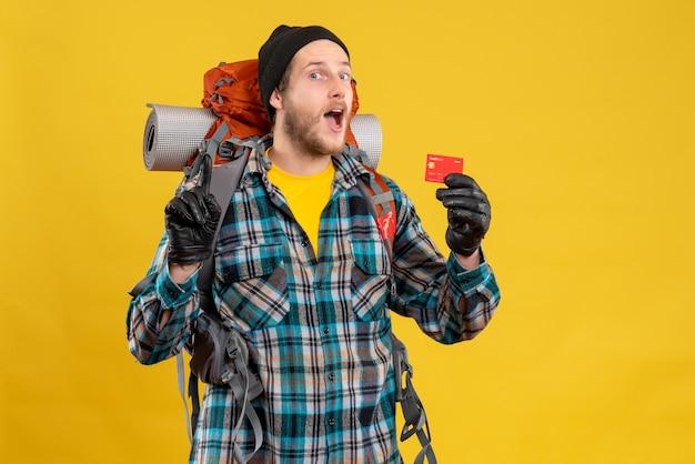 Vue de face du jeune homme barbu avec backpacker tenant une carte de crédit surprenante avec une idée