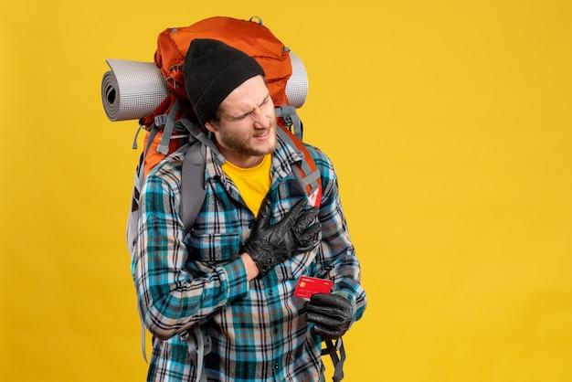 Vue de face du jeune homme barbu avec backpacker tenant une carte de réduction mettant la main sur sa poitrine