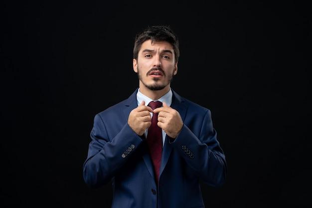 Vue de face du jeune homme barbu confus posant sur un mur sombre isolé