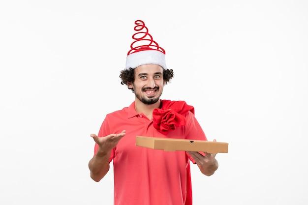 Vue de face du jeune homme avec une boîte de livraison de nourriture sur un mur blanc