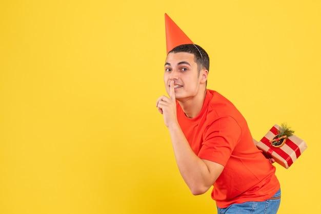 Vue de face du jeune homme cachant le cadeau de noël derrière son dos sur le mur jaune