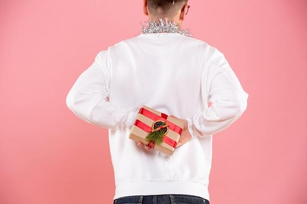 Vue de face du jeune homme cachant le cadeau de noël derrière son dos sur le mur rose